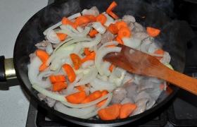 Кладем нашинкованный полукольцами лук и нарезанную морковь. Так же, не снижая огня и постоянно помешивая, обжариваем все вместе еще 4-5 минут.