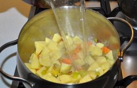Кладем нарезанную картошку и заливаем горячим бульоном. Без готового бульона – крошим в кастрюлю кубики и заливаем кипящей водой. Под крышкой варим при небольшом кипении 10-15 минут, до готовности картофеля.