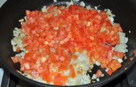 Лук и чеснок измельчаем, кладем в разогретое средним огнем масло, пассеруем 10 минут. Попутно помидоры, ошпарив кипятком и охладив, избавляем от шкурки и нарезаем мелкими кубиками. Добавляем в сковороду, тушим минут 8-10, до почти полного выпаривания жидкости.
