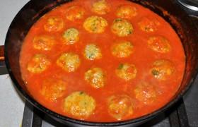 Закладываем их в томатный соус, из которого должны чуть выглядывать верхушки фрикаделек, осторожно переворачиваем или просто поливаем сверху соусом. И после закипания тушим на небольшом огне 20-22 минуты, под крышкой.