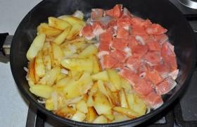 жарим 2-3 минуты, распускаем сливочное масло и выкладываем кубики рыбы. Можно смешать с картошкой, но лучше получается, если мы освобождаем для рыбы часть сковороды. Продолжаем жарить, посолив картофель, перемешивая и переворачивая и его, и рыбу, 3-4 минуты.