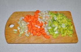 Для заправки этого супа мы не тратим время на мелкую нарезку: нарезаем средним кубиком сельдерей, лук, на 4 части делим вдоль, рубим поперек и морковь, и белую часть лука-порея. Раздавливаем плоской стороной ножа чеснок.