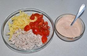 Готовое филе измельчаем тем или иным способом, отправляем в миску. Добавляем натертый крупно сыр, нарезанные на кусочки черри, рубленый зеленый лук. Солим и перчим.