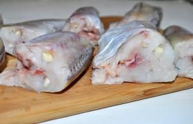 Когда рыбка немного обсохла –  нашпиговываем  ее кусочками чеснока, нарезанными вдоль. Рыба стала такой сочной и мягкой, что чеснок легко вдавливается пальцами.