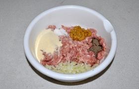 Фарш готовим сами, измельчаем в мясорубке только мясо. Луковицу рубим ножом совсем мелко, добавляем к мясу еще яйцо, соль и перец, горчицу и манку.