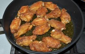 Масло в сковороде должно быть слоем не менее 3-4 мм. Раскладываем крылышки, жарим в разогретом масле на огне больше среднего до ярких румяных корочек: 4-5 минут одну и столько же вторую сторону.