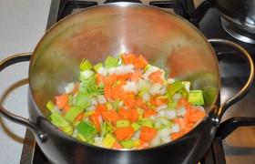 Нарезанные овощи загружаем в кастрюлю с толстым дном, где уже разогрелось на среднем огне масло. Ставим крышку, но закрываем неплотно. Помешивая каждые 1,5-2 минуты, слегка обжариваем в течение 9-10 минут.