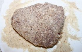 Поставив перекаливаться на сильный огонь сковороду с растительным маслом (слоем 6-8 мм), панируем мясо в сухарях .