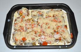 Половину овощей раскладываем на дне смазанной маслом формы, размещаем на них куски рыбы. Сверху – оставшиеся овощи. Солим, посыпаем перцем. Смешиваем сметану со стаканом оставленного молока и мелко тертым сыром, в соус добавляем пару долек измельченного чеснока. Заливаем рыбу.