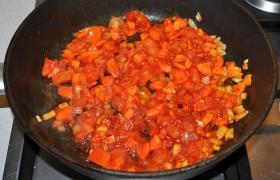 Засыпаем измельченный помидор - и еще минуты три не ленимся все это периодически мешать. Теперь добавляем томатную пасту, закипело - кладем тушенку. Вместе с тем соусом или желе, которое есть в банке. Добавляем еще чуть огня и, помешивая, держим на нем 3-4 минуты.
