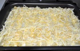 Форму отправляем в духовку, нагретую до 190-200°, на 25-30 минут. Затем вынимаем, посыпаем тертым сыром и запекаем еще 10-12 минут. Если каннеллони слипнутся в форме – это нормально. Лопаткой поделим на порции.