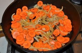 В той же сковороде – но уже на среднем огне – 10-12 минут пассеруем нашинкованный полукольцами лук и кружки моркови.
