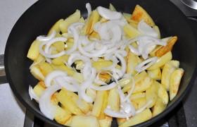 За те 8-9 минут, что жарится картофель (мы его переворачиваем периодически), очищаем и шинкуем половинками колец лук, а также снимаем филе рыбы с кожи и нарезаем кубиками. Солим и хорошо обрызгиваем лимонным соком, перемешиваем. Добавив к картошке лук,