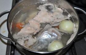 У нас была крупная замороженная горбуша, часть филе которой пошла на второе блюдо, а остальное – голову (без жабер), хвост, все кости и часть мякоти мы заложили в кастрюлю для бульона, залили водой, добавили лук и морковь, перец. После 20 минут варки вынимаем мякоть, а остальное варим еще 20-30 минут. Затем бульон процеживаем, кладем нарезанный картофель.