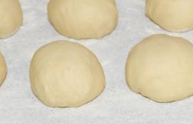 Делим тесто на равные части, скатываем шарики. Закончив с последним, начинаем раскатывать или разминать, растягивать руками лепешки. Можно смазать пальцы растительным маслом, но вовсе не обязательно.