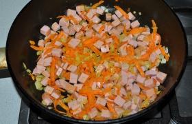 Нарезаем мелкими кубиками колбасу. Добавляем в сковороду к овощам, обжариваем 2-4 минуты.