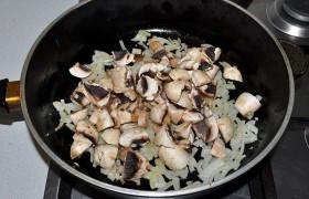 Ставим варить яйца. На второй конфорке 5-6 минут обжариваем на среднем огне нашинкованный лук. Добавляем нарезанные шампиньоны, сливочное масло, жарим 4-5 минут.