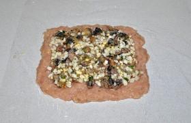 Раскладываем половину начинки, в которую к луку и грибам уже добавили нарезанные яйца и зелень, соль и перец. Слегка вминаем начинку в фарш.