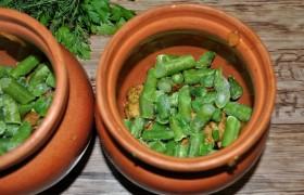 В горшочки распределяем поровну зеленую фасоль, нарезав ее кусочками или оставляя целой.