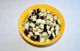 Начинаем с баклажанов: моем, срезаем плодоножку, нарезаем небольшим кубиком заливаем водой с солью или пересыпаем солью и ставим сверху груз.