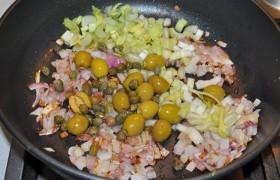 Пока в большой сковороде на огне чуть больше среднего разогревается масло, мелко шинкуем лук, пассеруем его до прозрачности 5-6 минут, помешивая. Добавляем оливки, каперсы и порубленные черешки сельдерея, тушим 4-5 минут.