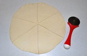 Срезав углы с квадратов теста, раскатываем его в круг диаметром примерно 28-30 см и делим на 6 частей.