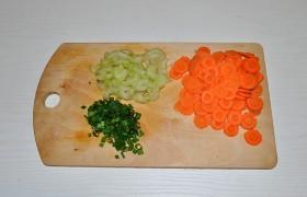 Подготавливаем овощи: тонко нарезаем морковь и сельдерей, что удобно делать на стороне терки, назначенной для шинковки капусты. Мелко рубим зеленый лук.