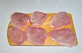 Нарезаем из куска корейки 6 шницелей 10-12 мм толщины. Слегка смазываем оливковым маслом и посыпаем травами, растирая их в пальцах, перцем. Похлопываем, чтобы приправа плотнее легла на мясо.